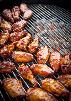 Sauced BBQ chicken wings over hot coals